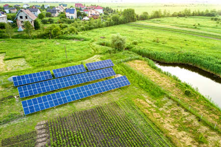 Blue solar photo voltaic panels mounted on metal frame standing on ground with green grass in field.