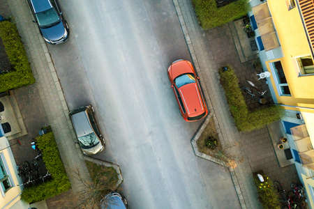 Aerial view of residential houses with red roofs and streets with parked cars in rural town area. Quiet suburbs of a modern european city. Zdjęcie Seryjne