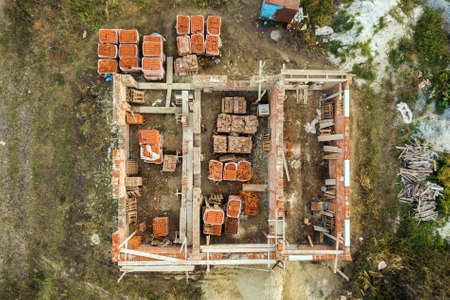 Aerial view of building site for future brick house, concrete foundation floor and stacks of yellow clay bricks for construction. Zdjęcie Seryjne