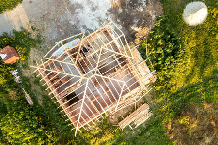 Aerial view of unfinished brick house with wooden roof structure under construction.