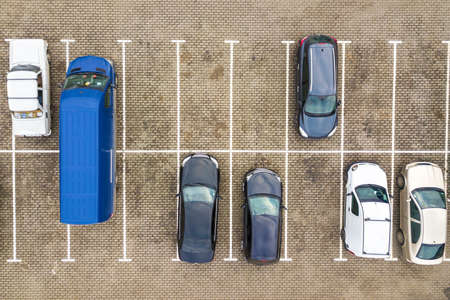 Top down aerial view of many cars on a parking lot of supermarket or on sale car dealer market. Zdjęcie Seryjne