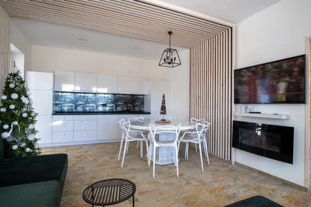 Interior of modern spacious kitchen with white walls, decorative wooden elements, contemporary furniture and big soft couch.