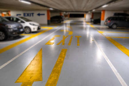 Yellow markings with blurred modern cars parked inside closed underground parking lot. Zdjęcie Seryjne