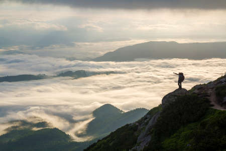 Wide mountain panorama. Small silhouette of tourist with backpack on rocky mountain slope with raised hands over valley covered with white puffy clouds. Beauty of nature, tourism and traveling concept Фото со стока