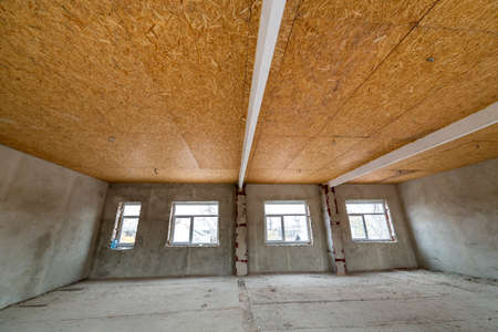 Unfinished apartment or house big loft room under reconstruction. Plywood ceiling, plastered walls, window openings, cement floor. Construction and renovation concept. Stockfoto
