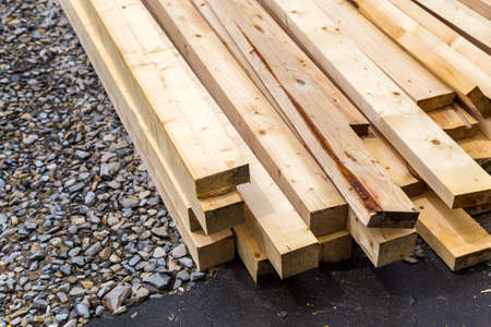 Stack of natural wooden boards on building site. Industrial timber for carpentry, building or repairing, lumber material for roofing construction.