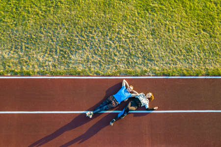 Top down aerial view of two young people sportsman and sportswoman laying on red rubber running track of a stadium field resting after jogging marathon in summer.