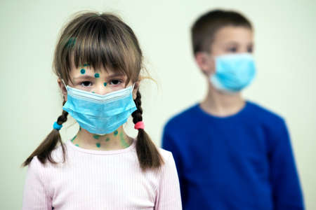 Boy and girl wearing blue protective medical mask ill with chickenpox, measles or rubella virus with rashes on body. Children protection during epidemic of coronovirus. Covid-19 contagion concept. Stock Photo