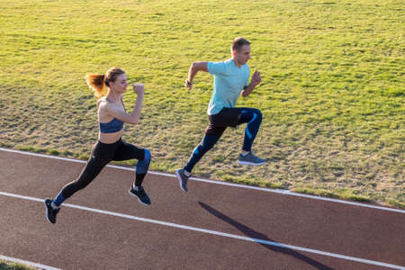 Young couple of fit sportsmen boy and girl running while doing exercise on red tracks of public stadium outdoors.
