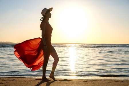 Young woman wearing long red dress and straw hat standing on sand beach at sea shore enjoying view of rising sun in early summer morning. 写真素材 - 143208562