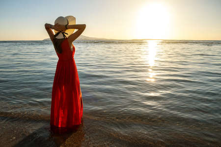 Young woman wearing long red dress and straw hat standing in sea water at the beach enjoying view of rising sun in early summer morning. 写真素材 - 143208570