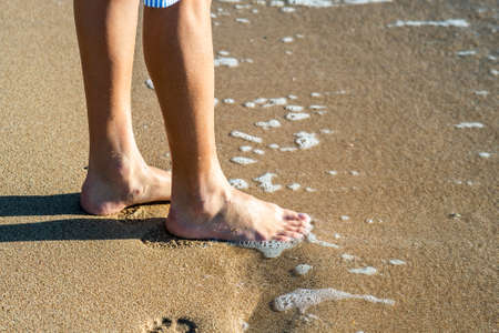 Close up of woman feet walking barefoot on sand beach in sea water. Vacation, travel and freedom concept. People relaxing in summer. Stock Photo