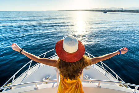 Young woman with long hair wearing yellow dress and straw hat standing with raised hands on white yacht deck enjoying view of blue sea water.
