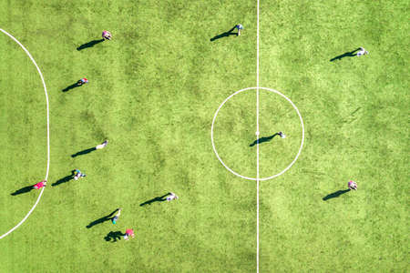 Top down aerial view of green football sports field and players playing football. Drone taken image of small unrecognizable sportsmen on grass covered stadium during sport activities. Stock Photo