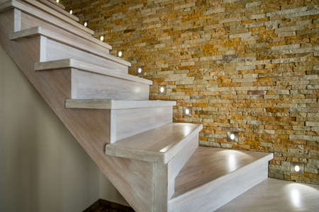Stylish wooden contemporary staircase inside loft house interior. Modern hallway with decorative limestone brick walls and white oak stairs. Banque d'images - 143513694