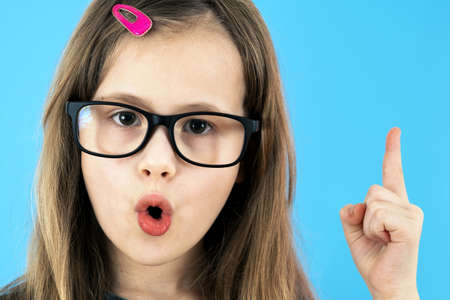 Close up portrait of a child school girl wearing looking glasses holding up point finger in I have an idea gesture isolated on blue background.