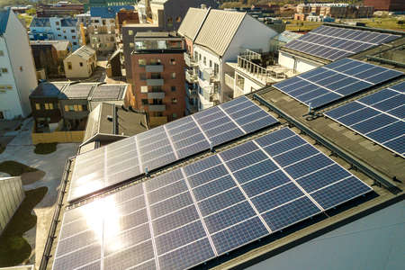Aerial view of solar photovoltaic panels on a roof top of residential building block for producing clean electric energy. Autonomous housing concept.