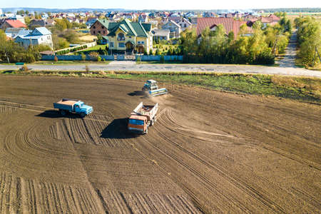 Aerial view of a tractor plowing black agriculture farm field after harvesting in autumn.