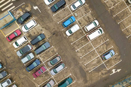 Top down aerial view of many cars on a parking lot of supermarket or on sale car dealer market. Stock Photo