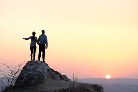 Man and woman hikers standing on big stone at sunset in mountains. Couple on high rock in evening nature. Tourism, traveling and healthy lifestyle concept. Stockfoto