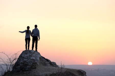 Randonneurs homme et femme debout sur une grosse pierre au coucher du soleil dans les montagnes. Couple sur haut rocher dans la nature du soir. Concept de tourisme, de voyage et de mode de vie sain. Banque d'images