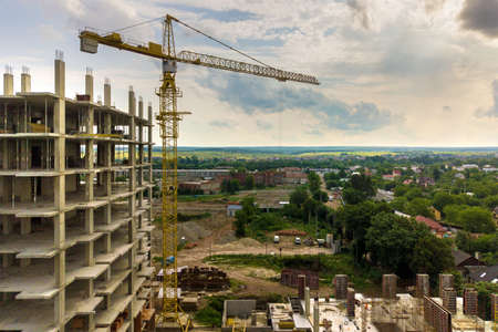 Aerial view of tower lifting crane and concrete frame of tall apartment residential building under construction in a city. Urban development and real estate growth concept.