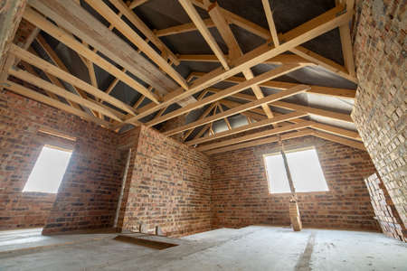 Interior of unfinished brick house with concrete floor, walls ready for plastering and wooden roofing frame attic under construction. Stockfoto