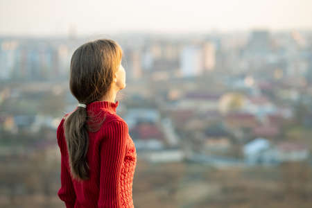 Young woman in red jacket standing outdoors enjoying evening view. Relaxing, freedom and wellness concept. 写真素材