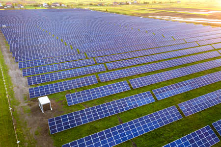 Large field of solar photo voltaic panels system producing renewable clean energy on green grass background. Stockfoto