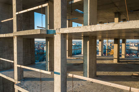 Interior of a concrete residential apartment building room with unfinished walls and support pillars for future walls under construction.