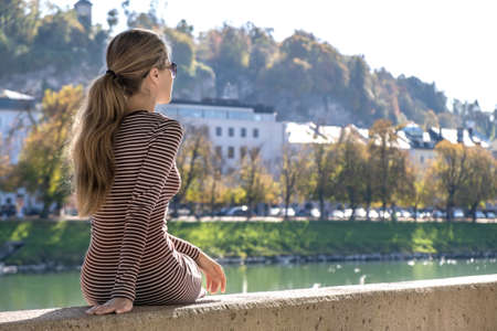 Young woman in a casual dress and sunglasses resting outdoors on a warm autumn day. Standard-Bild