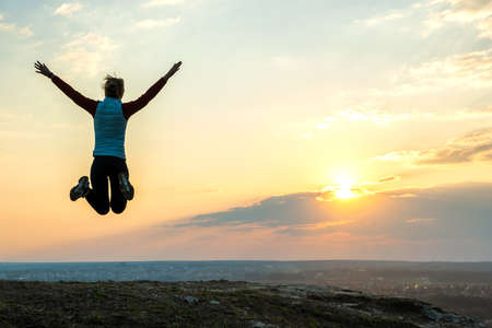 Silhouette of a woman hiker jumping alone on empty field at sunset in mountains. Female tourist raising her hands up in evening nature. Tourism, traveling and healthy lifestyle concept.