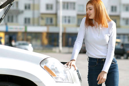 Young stressed woman driver near broken car with popped hood having a prbreakdown problem with her vehicle waiting for assistance.