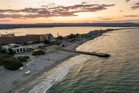 Aerial view of Pomorie city that is located on Black Sea shore. Top view of sand beaches with many hotel buildings and tourist infrastructure.