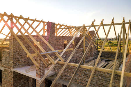Unfinished brick house with wooden roof structure under construction. Banque d'images