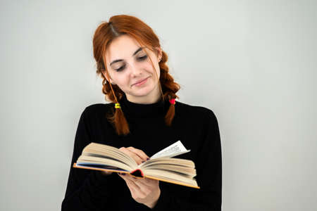 Young pretty girl read an open book in her hands. Reading and education concept. Imagens