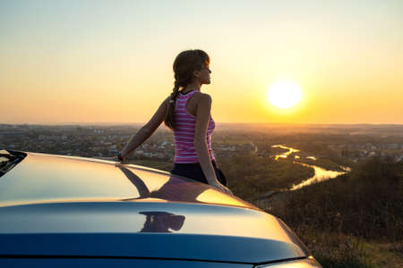 Young woman driver standing near her car enjoying warm sunset view. Girl traveler leaning on vehicle hood looking at evening horizon.