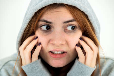 Close up portrait of scared young redhead woman wearing warm hoodie pullover.