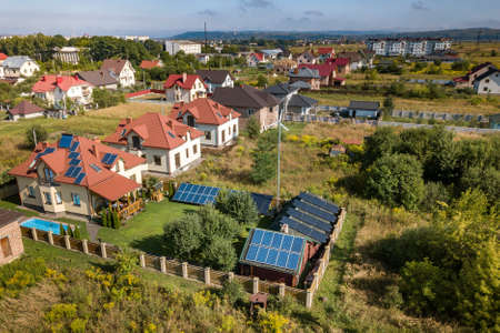 Aerial view of a new autonomous house with solar panels, water heating radiators on the roof, wind powered turbine and green yard with blue swimming pool. Stock Photo