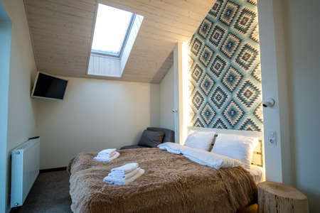 Interior of a spacious hotel bedroom on attic floor with fresh linen on a big double bed. Cozy contemporary mansard room in a modern house.
