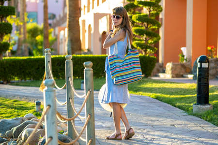 Young woman wearing light blue summer dress holding fashionable shoulder bag and yellow straw hat standing outside enjoying warm weather in summer park.