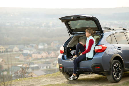 Young woman driver sitting alone in her car enjoying view of nature landscape. Standard-Bild