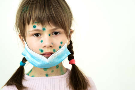 Child girl wearing blue protective medical mask ill with chickenpox, measles or rubella virus with rashes on body. Children protection during epidemic of coronovirus. Covid-19 contagion concept.