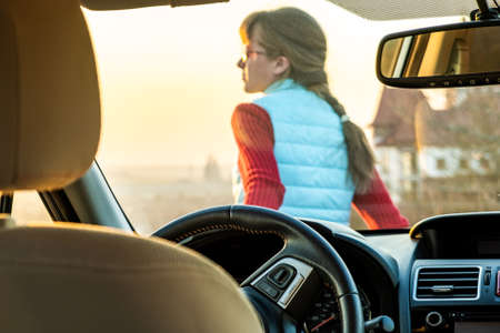 View from inside of a young woman standing near her car enjoying warm sunset view. Girl traveler leaning on vehicle hood looking at evening horizon.