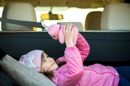 Pretty happy child girl playing with a pink toy teddy bear in a car trunk. Standard-Bild