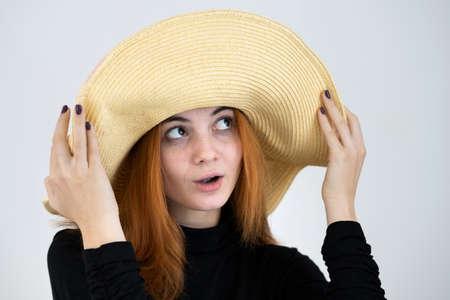 Portrait of funny redhead woman in bag yellow straw hat. Standard-Bild