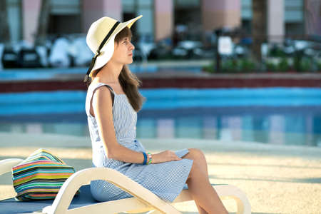 Young woman wearing light summer dress and yellow straw hat sitting outside near hotel swimming pool on summer sunny day. Standard-Bild