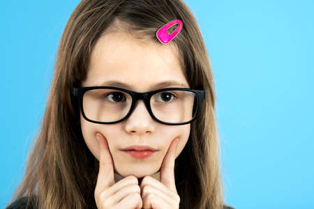 Close up portrait of a child school girl wearing looking glasses holding hand to her face thinking about something isolated on blue background. Standard-Bild