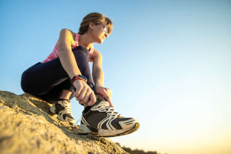 Woman hiker tying shoe laces of her sport boots while climbing steep big rock on a sunny day. Young female climber overcomes difficult climbing route. Active recreation in nature concept.