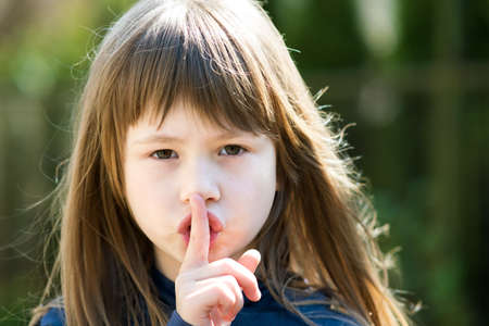 Portrait of pretty child girl with gray eyes and long hair holding point finger on her lips with hush sigh. Cute female kid on warm summer day outside. Standard-Bild